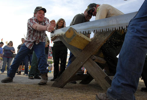 Two boys compete in log saw contest.
